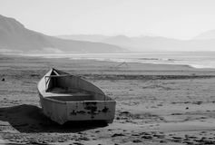 Black white image of a boat on the sea shore, after the storm Royalty Free Stock Image