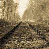 Black and white image of an old train line in a straight line, losing itself on the horizon. With trees on both sides in an autumn day with a blurred background stock photography