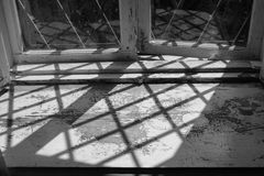 Black and white image of old wooden windowsill. Black and white image of old wooden aged peeled paint windowsill with grid shadow Stock Photography
