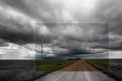 Black and white image of prairie storm with gravel road leading to horizon stock photography