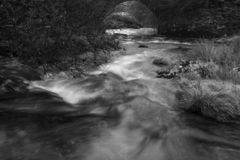 Black and white image of a river running under the B3357 on Dartmoor. Landscape aspect with slow shutter speed royalty free stock image