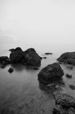 Black and white image of rock over the beach background Stock Photos