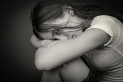 Black and white image of a sad and lonely girl. With her head resting on her legs and looking at the camera Royalty Free Stock Images
