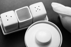 Black and white image of salt and pepper shakers, sugar-bowl and paper napkin holder in the wooden table. Stock Images