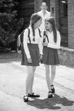Black and white image of schoolgirls talking while going to school royalty free stock photos