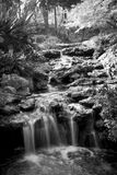 Black and White Image of Serene Garden Waterfall. Serene waterfall in garden setting, black and white Royalty Free Stock Photos