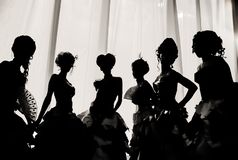Black and white image of the silhouette of girls and women in carnival costumes and ball dresses in the theater on the stage behin
