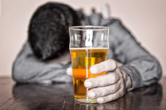 Black and white image of a sleeping drunk man. (only his beer is in color Royalty Free Stock Image