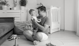 Black and white image of smiling toddler son hugging his father and looking at him. Black and white photo of smiling toddler son hugging his father and looking Royalty Free Stock Photos