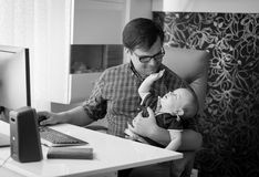 Black and white image of smiling young man working in home office and looking after his baby son royalty free stock image