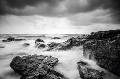 Black and white image,soft wave flow hitting the sandy beach. Over dark cloud background. soft focus image due to long exposure shot Stock Images