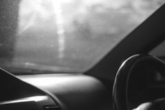 Black and white image steering wheel inside a car. On the road Stock Image