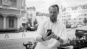 Black and white photo of stylish man with beard leaning on bicycle and using mobile phone. Black and white image of stylish man with beard leaning on bicycle and Royalty Free Stock Photo