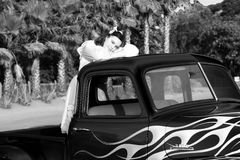 Black and white image of teen girl in pickup truck. A smiling, multicultural (asian/caucasian) teenager in pink poodle skirt and white blouse, stands in the back Royalty Free Stock Photos