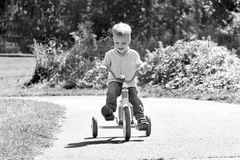 Black and white image of a toddler boy riding a Royalty Free Stock Image