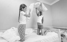 Black and white image of two girl having pillow fight at pajamas. Black and white photo of two girl having pillow fight at pajamas party stock images