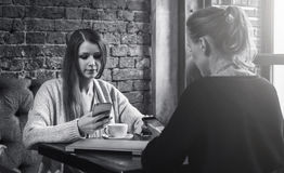 Black and white image. Two young women sitting in a cafe at the table and using smartphones. Royalty Free Stock Photos