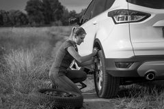 Black and white image of upset young woman changing car wheel on Stock Photo