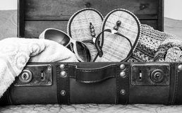 Black and white image of vintage leather suitcase packed with tr Stock Photo