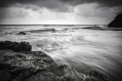 Black and white image wave flow on the sandy and rocky beach Stock Photos