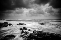 Black and white image wave hitting the coastline with dramatic cloud Royalty Free Stock Photo