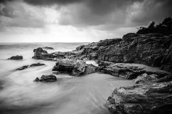 Black and white image of wave hitting the rock. dark and dramatic clouds. Stock Photos