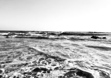 Black and white image of waves crashing into the rocks royalty free stock photography