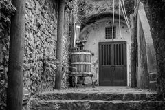 Black and white image with wine press and closed doors. Old Ital royalty free stock photo