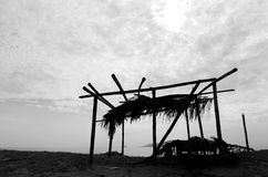 Black and white image of wooden cottage the sea with cloudy sky Stock Photo