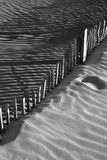 Black and white image of wooden fence in sand dunes Royalty Free Stock Images
