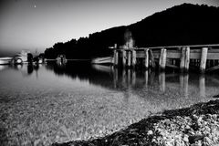 Agnontas beach and bay, Skopelos, Greece. Black and white image of wooden pier at Agnontas beach at night stock photos