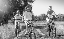 Black and white image of young mother riding on bicycles with tw Royalty Free Stock Photo