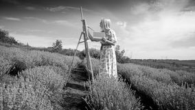 Black and white image of young woman in long dress painting picture of field royalty free stock images