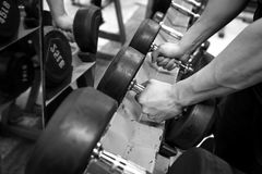 Black and white images Hand holding dumbbell in the gym. Bodybuilding royalty free stock image