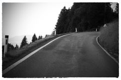Black and white images of highway in a curbe. Horizon bond wiht the asphalt road. Black and white photo stock photo