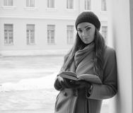 Black and white. interesting girl near the wall with a book. Beautiful girl with book near the walls of the arch, black and white Royalty Free Stock Images