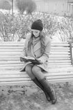 Black and white. interesting girl on a Park bench with a book, portrait Stock Image