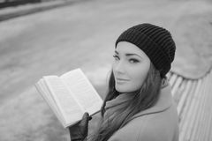 Black and white. interesting girl on a Park bench with a book Stock Images