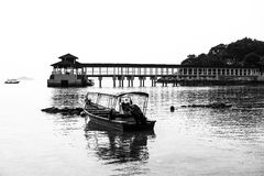 Black and white of jetty and fishing boats, Coral Bay, Perhentian Island Kecil, Malaysia Stock Photos