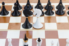 Black and white knights in front of black chess Stock Photo