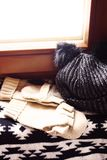 Black Scarf, gloves and hat with pompoms on windowsill royalty free stock photos