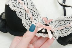 Black with white lace bodice in a female hand. Fashionable conce. Pt. Close-up Stock Photo