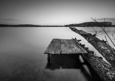 Black and white lake landscape with small wooden pier Royalty Free Stock Image