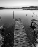 Black and white lake landscape with small wooden pier Stock Photos