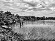 Black and white lake view. A black and white landscape view of the shore of a wooded lake with a small boat tied on the water's edge Royalty Free Stock Image