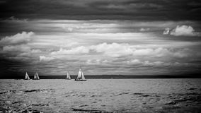 Black and white lake view with sailing boats and clouds overcast sky Stock Photo