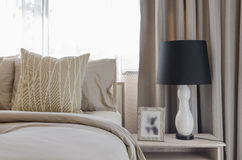 Black and white lamp on wooden table in luxury bedroom Royalty Free Stock Images
