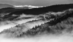 Black and White landscape image of hills. With early morning fog lifting stock photography