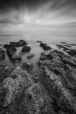 Black and white landscape looking out to sea with rocky shore an Stock Photos