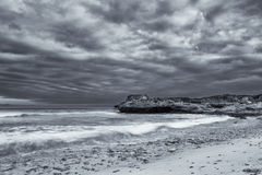 Black and white landscape of ocean rocks and clouds artistic con Stock Images